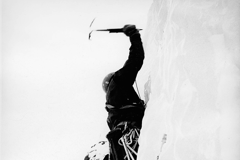 Thomas places his ice axe as he assends a frozen waterfall with Norrøna gear.
